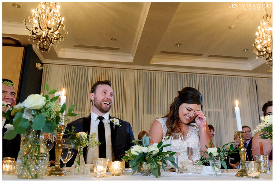 Bride and groom laughing and embarrassed at their parents' wedding toast.