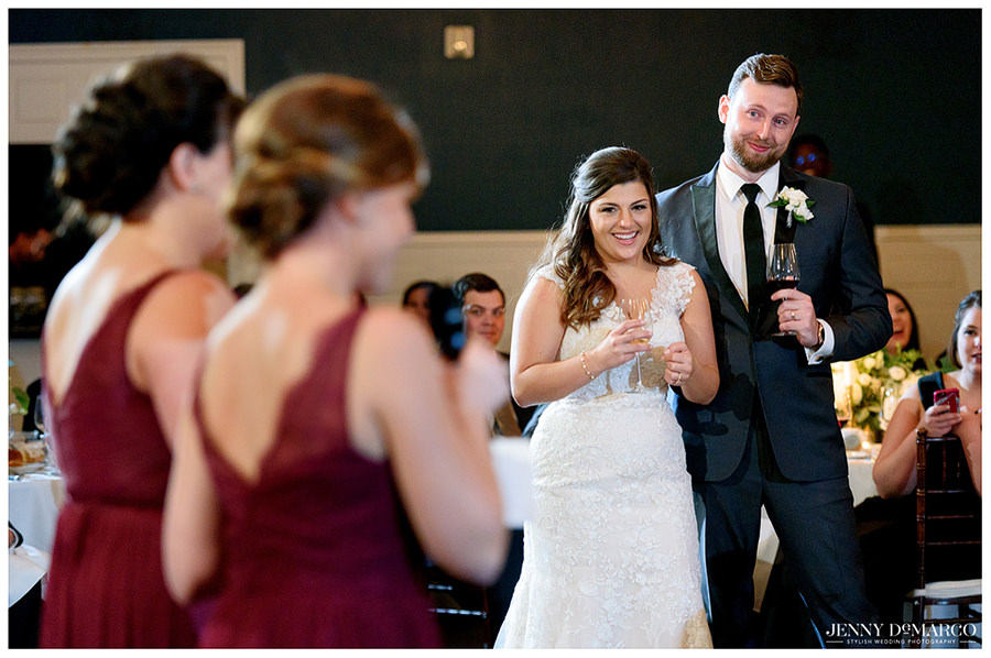 Bride and groom smiling at Bridesmaid's after sharing their toast.