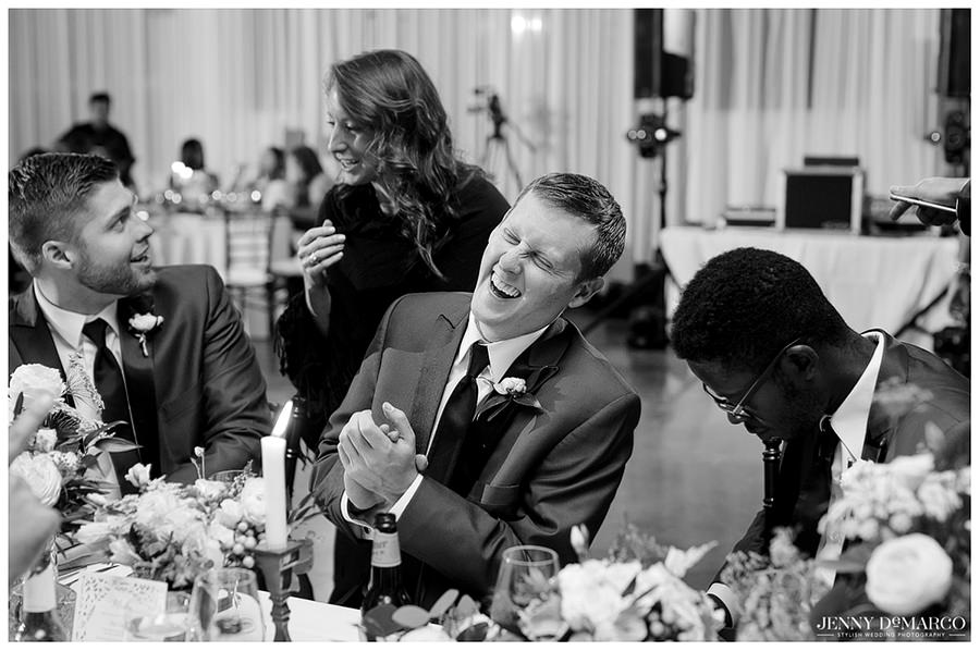 Wedding guest cracking up at a toast delivered by one of the groomsmen