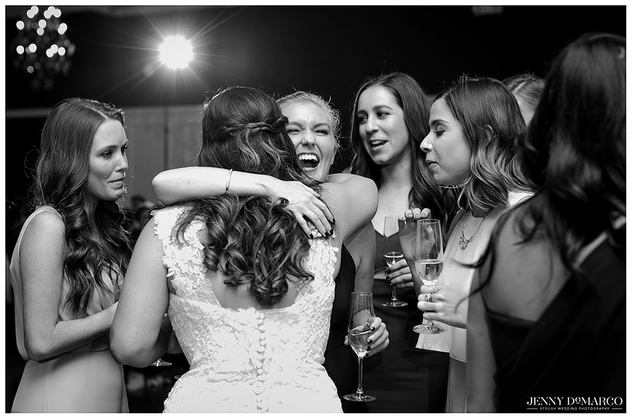 Bride hugging her smiling friend who is congratulating her new marriage.