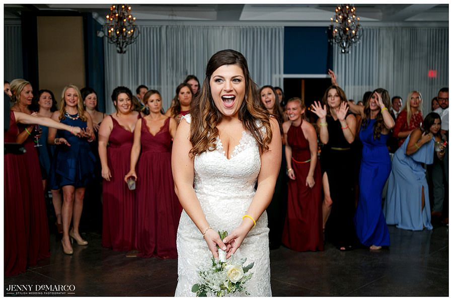 Bride about to toss bouquet into a sea of giddy girls
