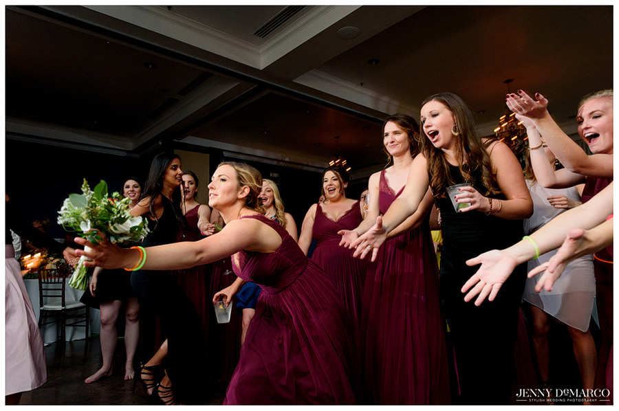Bridesmaids and wedding guests fighting to catch the brides' bouquet
