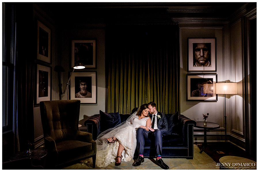 Bride and groom sharing an intimate moment on the couch of Hotel Ella.