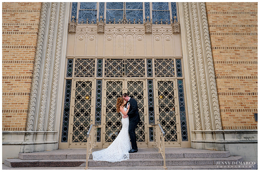 Bride and groom kissing in front of the iron gates at Central Christian Church