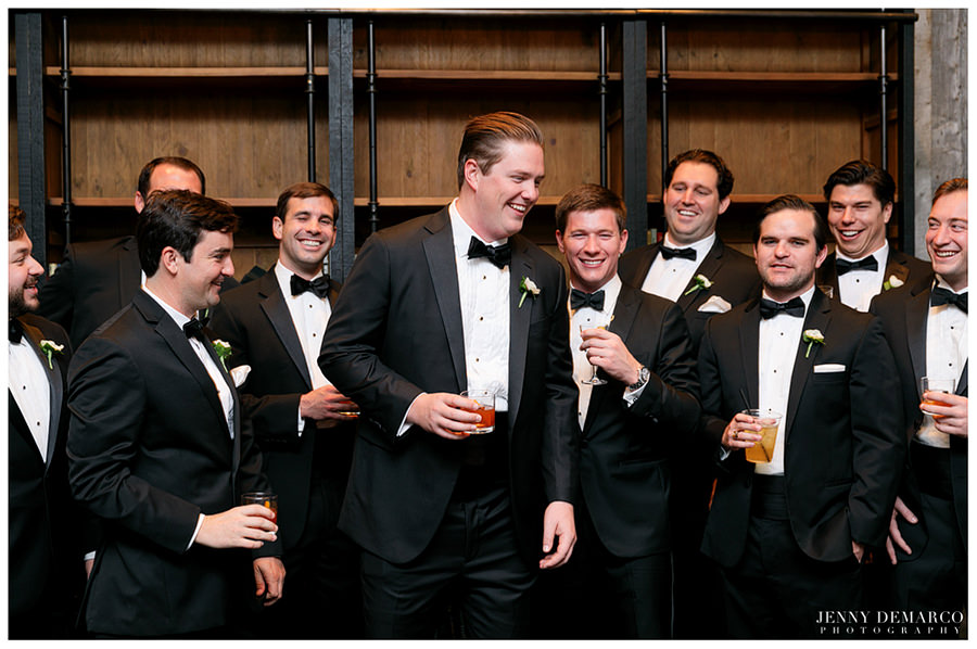 Groom and groomsmen having drinks and laughing before wedding at Central Christian Church