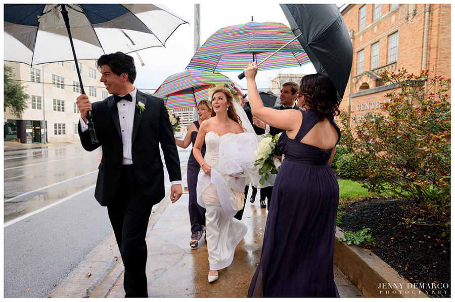 Wedding party walking in the rain with umbrellas towards Central Christian Church