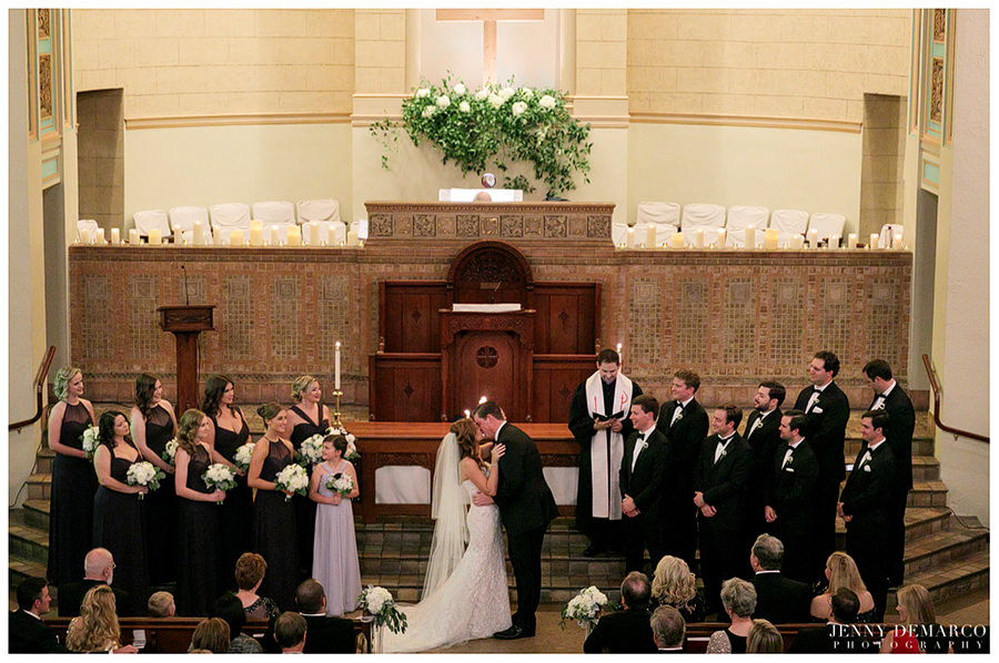 Bride and groom sharing their first kiss as a newly wed couple at Central Christian Church