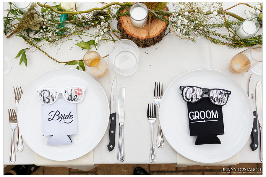 The Bride and Grooms places at the table with custom bride and groom glasses and koozies.