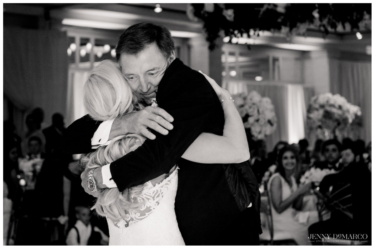 Father of the bride hugs the bride after their father-daughter dance