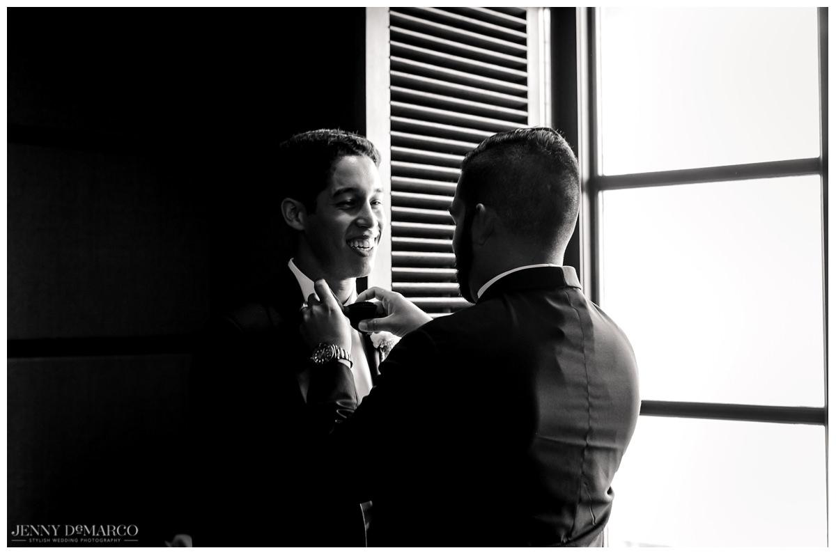 Groomsman helping groom get his tuxedo on before the wedding in Austin