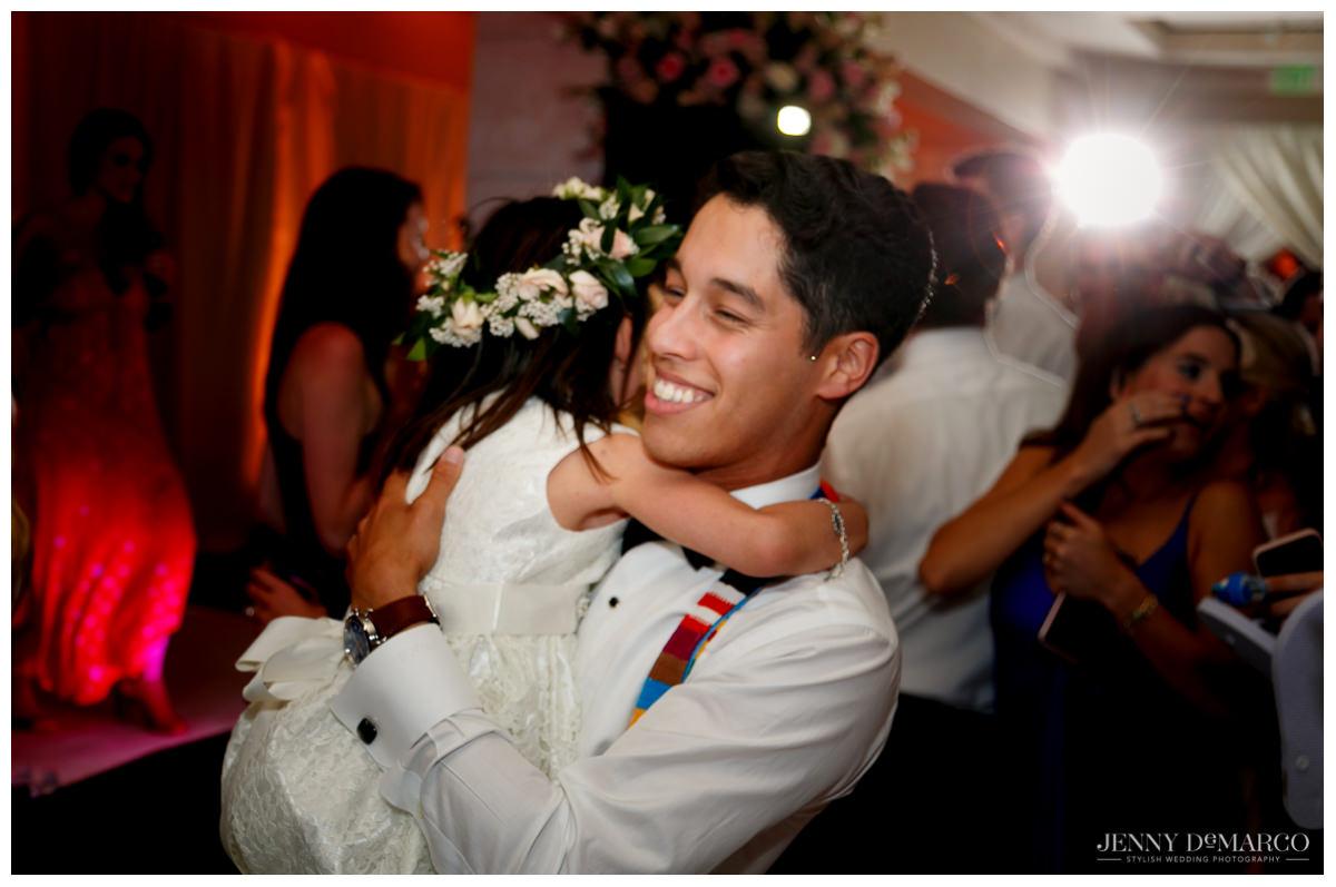 Groom hugs flower girl at wedding in Austin