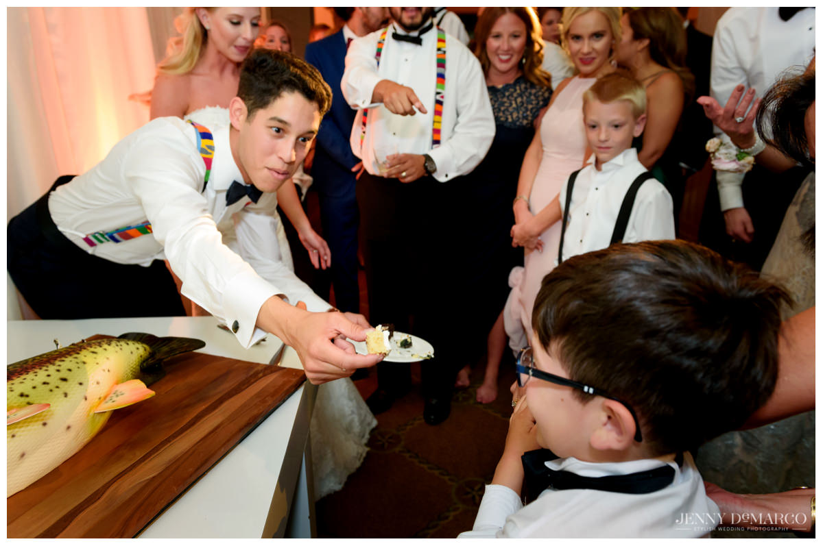 Groom hands sweet treats cake to a wedding guest in austin, texas