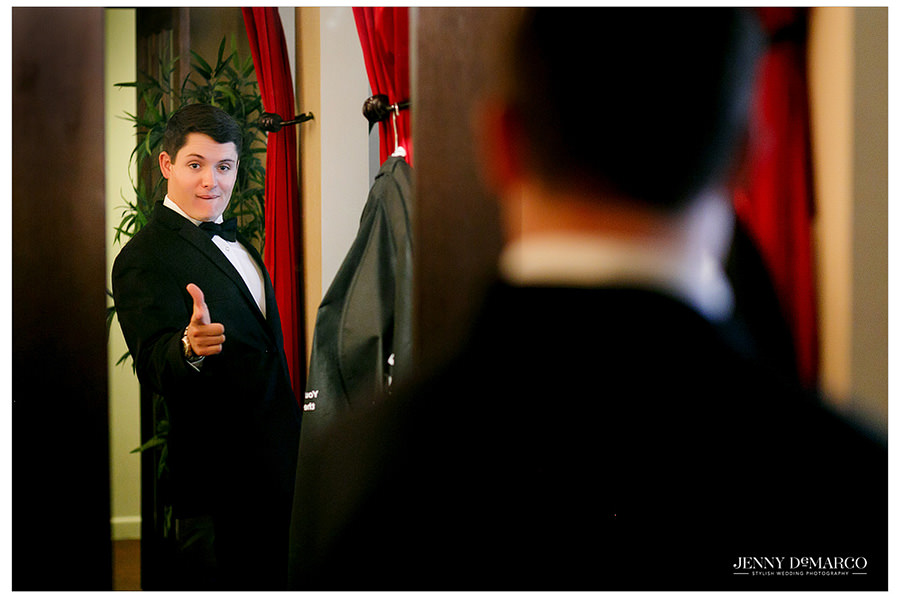 Funny shot of the groom checking himself out in the mirror