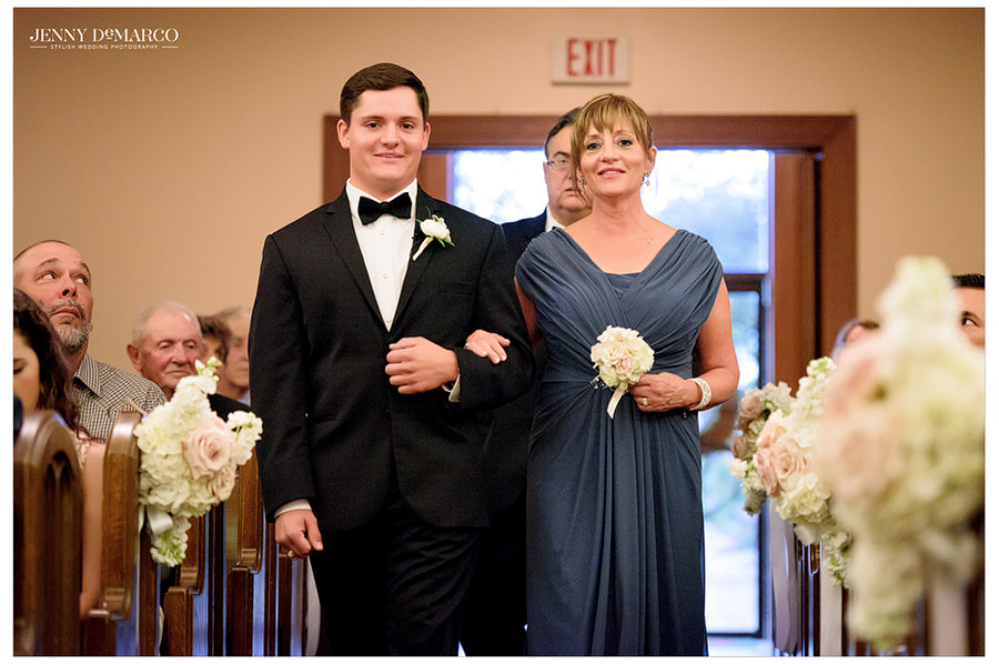 Groom and his mother walk down the aisle