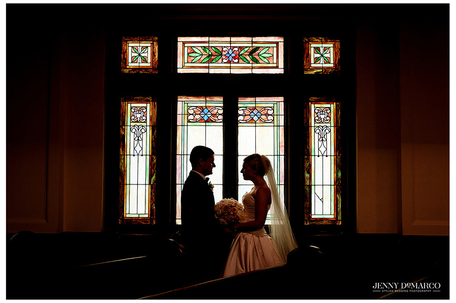 Bride and Groom silhouette in front of stained glass window of church
