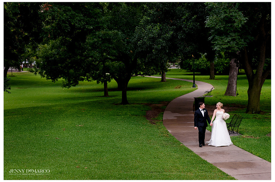 Bride and Groom stroll through the park in front of the Capitol in Austin