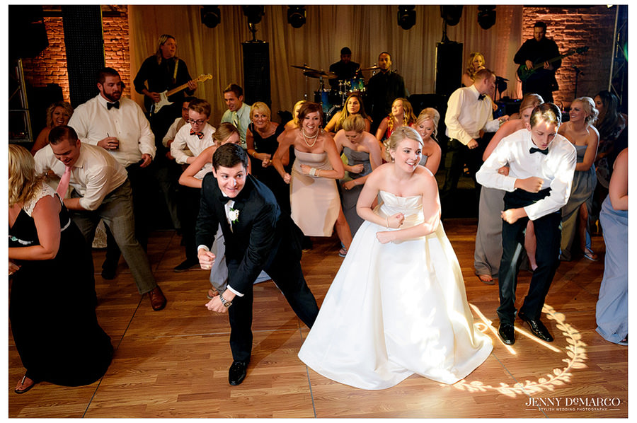 Bride and groom dance with guests at wedding reception