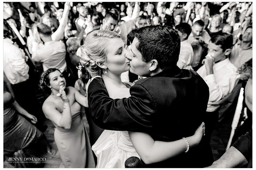 Bride and groom share a kiss at wedding reception