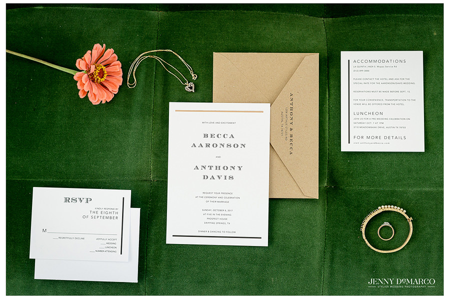 Beautiful invitations and the bride's jewelry on green velvet