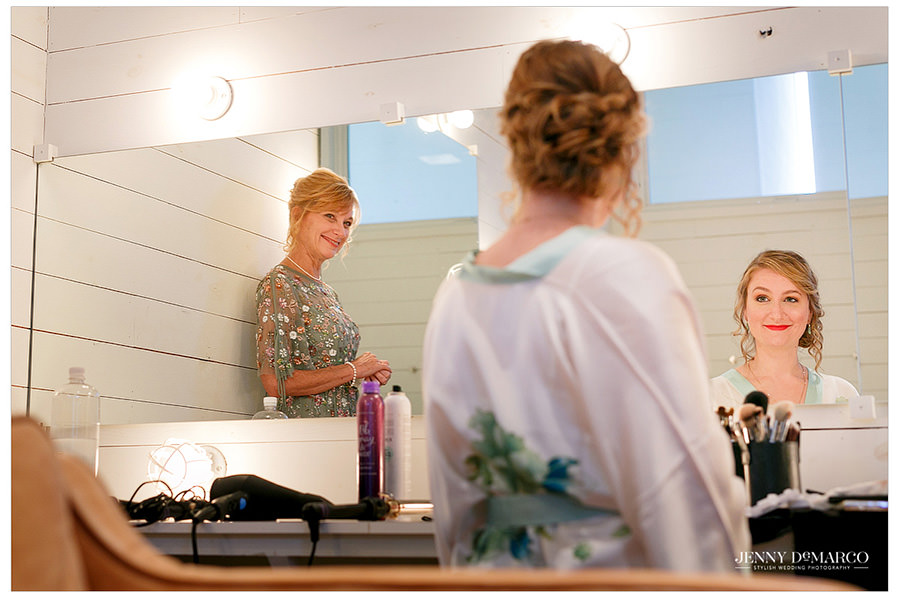 Bride smiling sweetly at her mother as they get ready for the big day