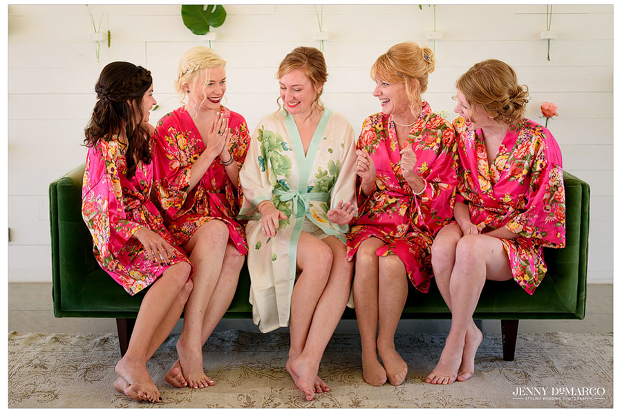 Bride and bridesmaids in modern floral robes as they giggle and get ready