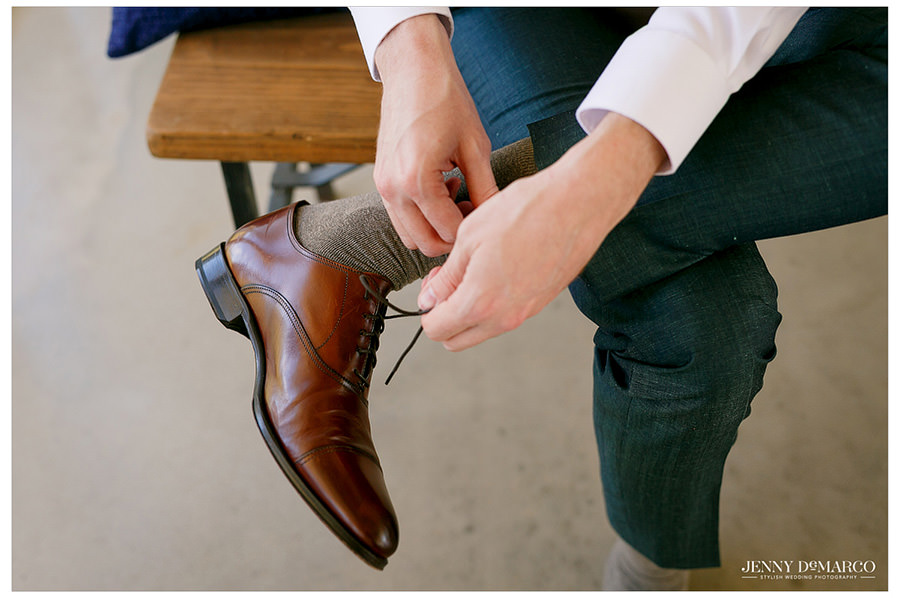 Groom ties his shoes before his wedding