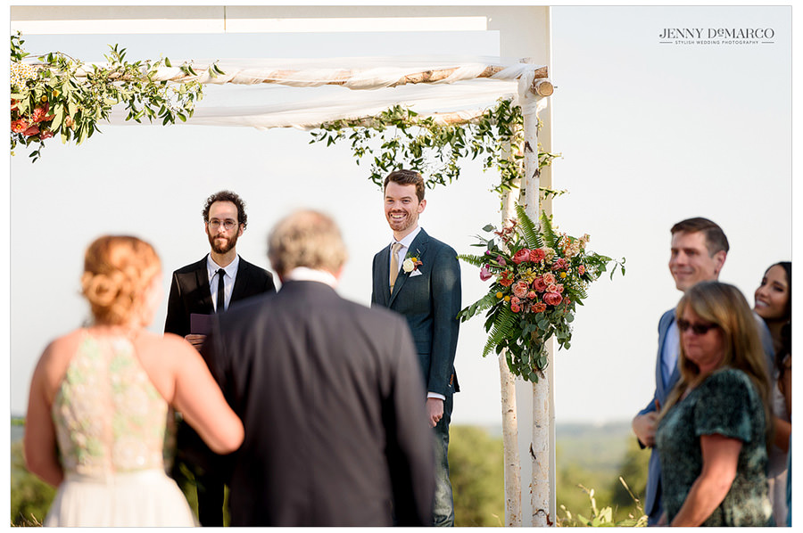Groom stares at his bride walking down the aisle