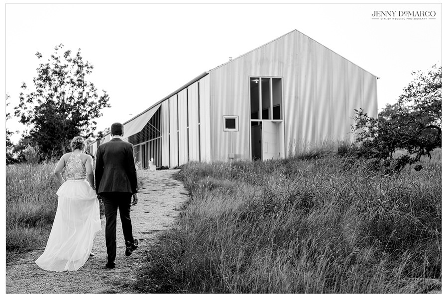 black and white shot of bride and groom walking to their reception