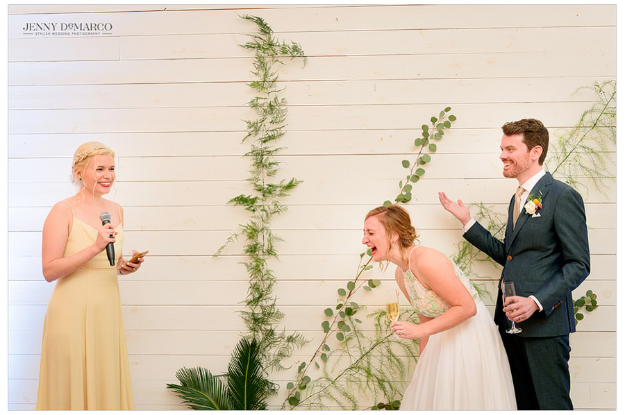 Bride laughing as her best friend gives a wedding toast