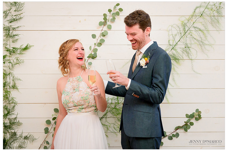 Bride and groom laughing during their toast