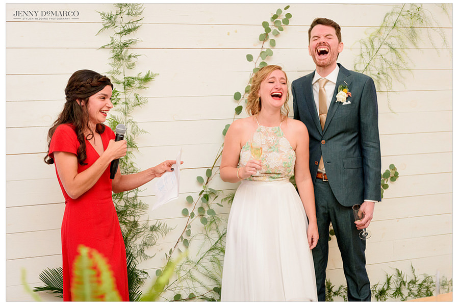 Bride laughing as her best friend gives a toast