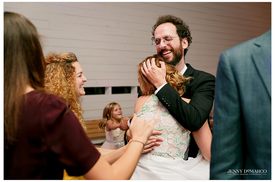 Bride and officiant hug at the wedding reception