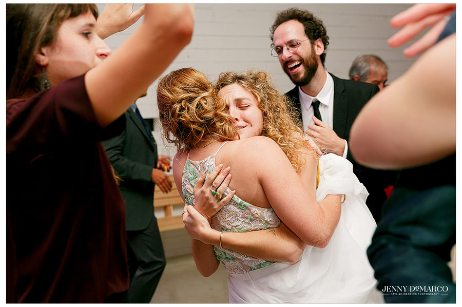 Bride and friend hug at the wedding reception