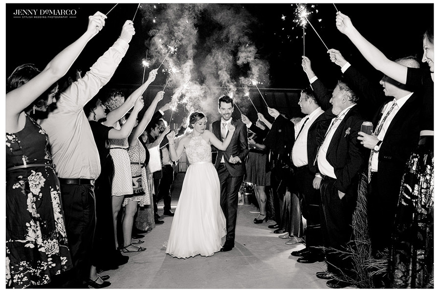 Black and white shot of bride and groom leaving their wedding