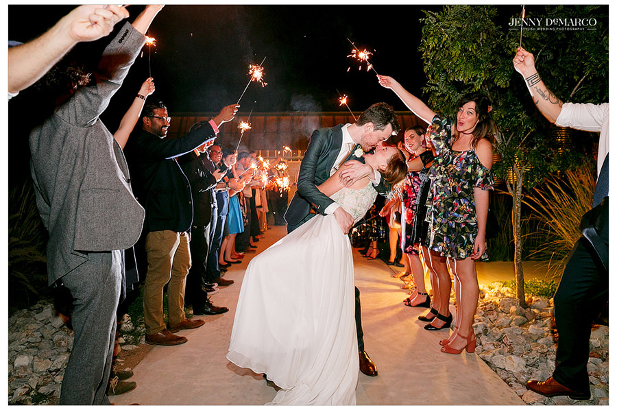 Bride and Groom kiss as their friends hold out sparklers