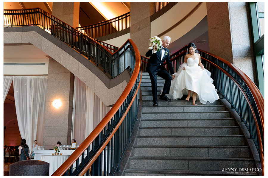 Father of the bride carries her shoes while they ascend down the staircase.