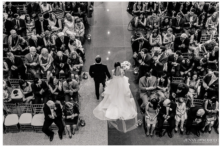 Looking down as the bride and groom exit.