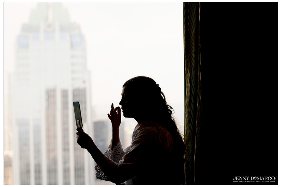 Bride applying makeup with the Frost Bank tower in the background.