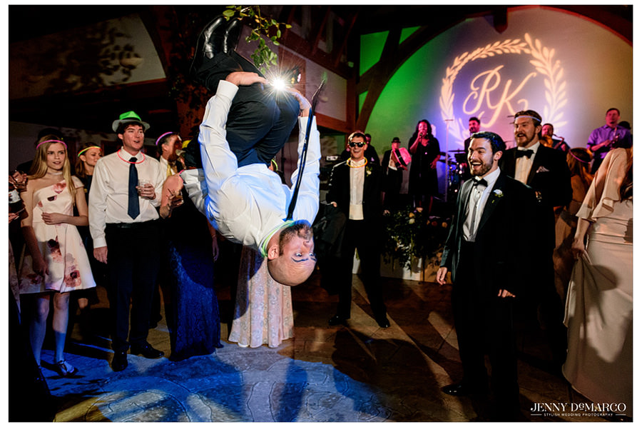 Groomsmen doing a backflip on the dance floor.