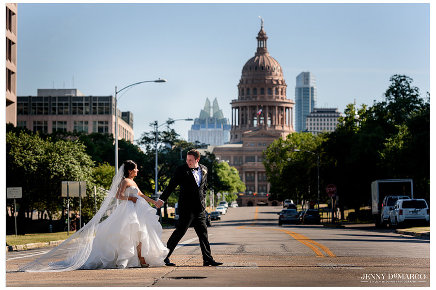 Bride and groom walking across the street with the Texas State Capitol in downtown Austin.