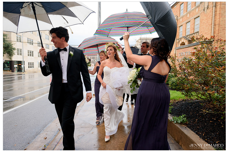 Bride being escorted under umbrellas to the ceremony.