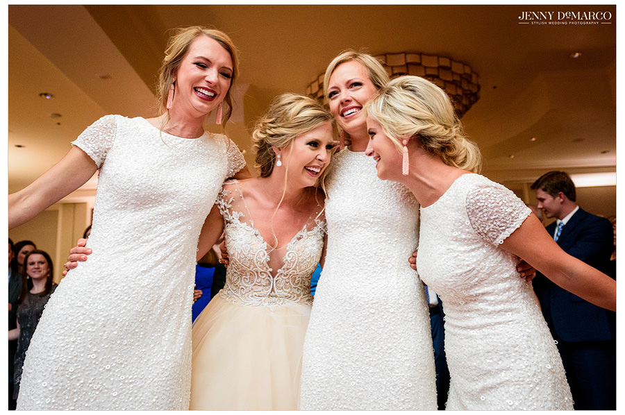 Bride hugging her bridesmaids on the dance floor at the reception