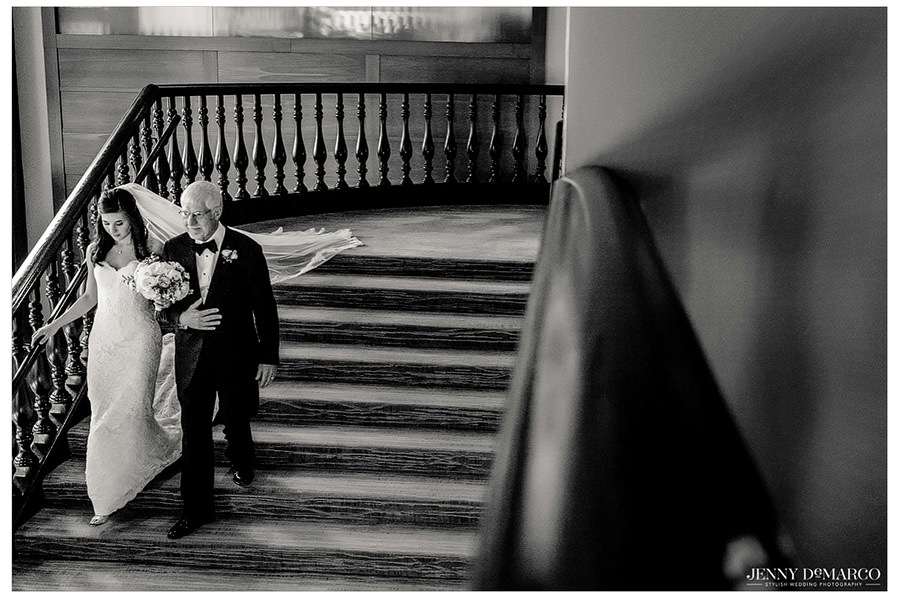 Father of the bride escorting his daughter down the stairs toward the ceremony.