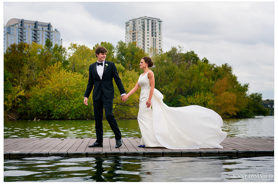 Wind blowing brides train as the walk along the board walk on Town lake in downtown Austin.