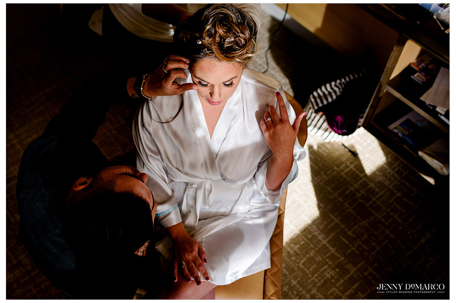 Arial photo of bride in robe getting her makeup done on her wedding day.