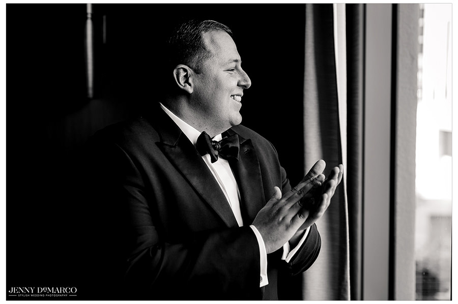 Black and white photo of groom looking out the window in anticipation for the ceremony to start.
