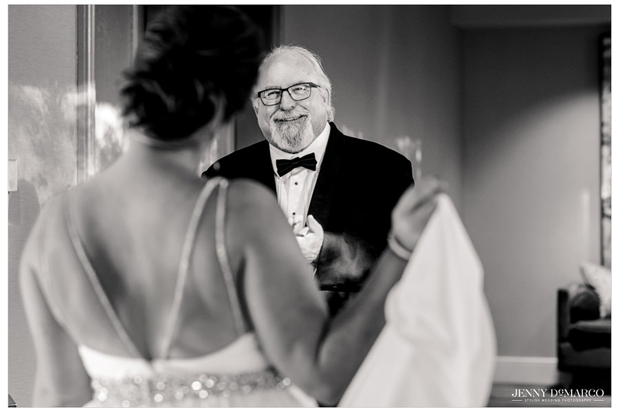 The father of the bride sees his daughter in her wedding dress for the first time.