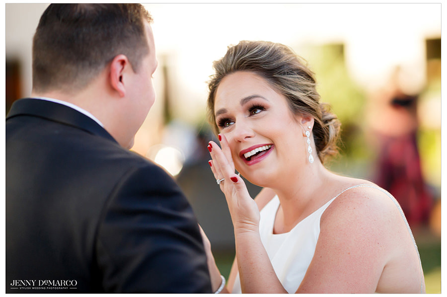 The bride wipes a tear away as she happily looks at her groom.