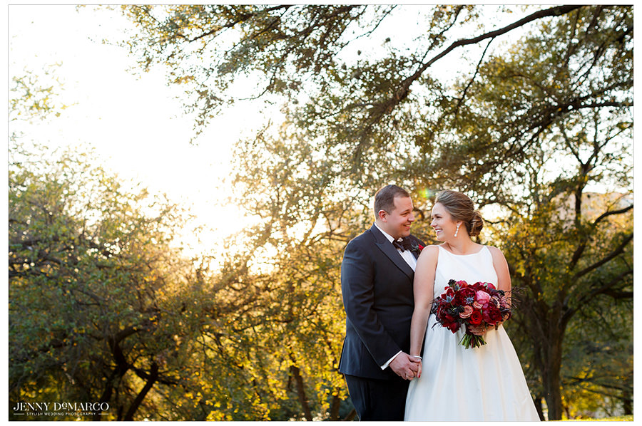 The bride and groom look lovingly at one another as the light peaks through the trees and frames the happy couple.