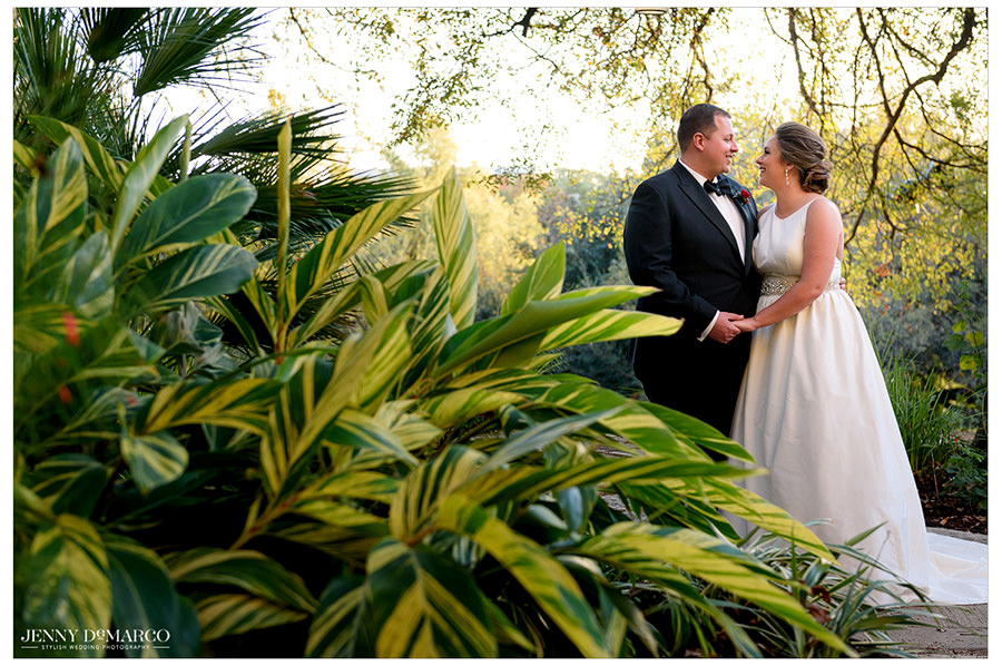 The bride and groom smile at one another, framed by foliage and natural light.